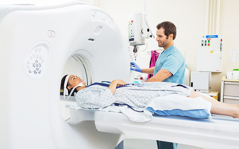 Doctor having a patient go into a CAT scan