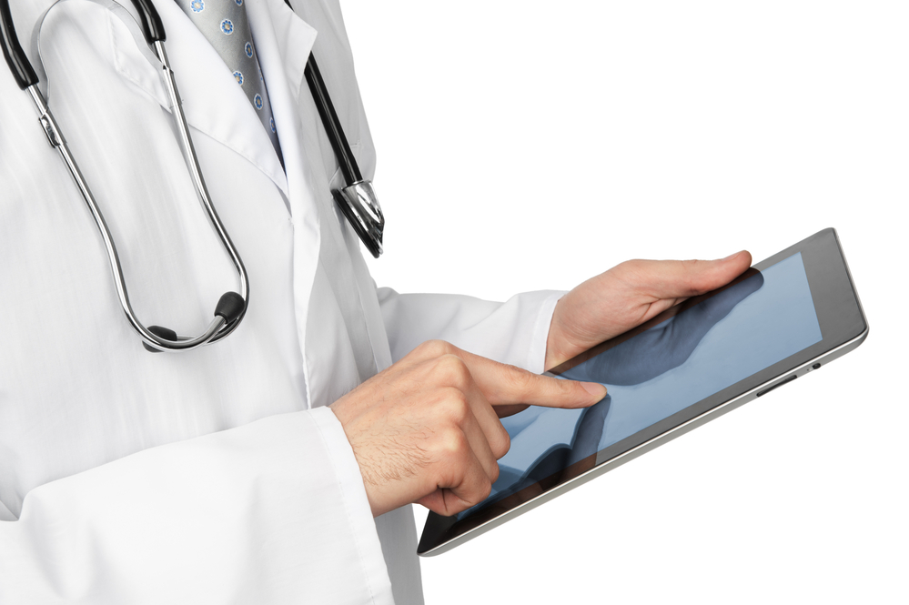 Doctor in white lab coat with stethoscope using a tablet computer
